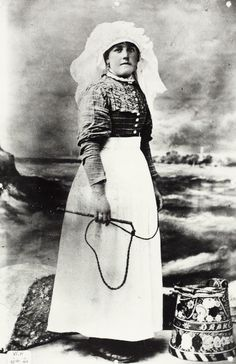 Studio photo taken by Wakefields of Brentford showing a boatwoman in full dress including a bonnet, and holding a cracking whip. She is stood beside a decorated can and in front of a coastal scene. Canal Barge, Brentford, Fashion Plates, Boating, Regional, Photo Studio, Traditional Outfits, Evolution, Britain