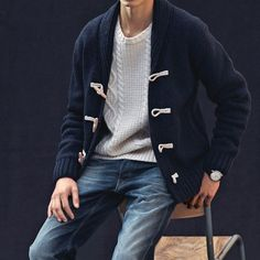 Dress in a navy duffel cardigan and navy jeans for a trendy and easy going look.  Shop this look for $77:  http://lookastic.com/men/looks/white-cable-sweater-navy-duffle-cardigan-navy-jeans/6590  — White Cable Sweater  — Navy Duffle Cardigan  — Navy Jeans