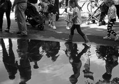 Children walking around a puddle in Kelvingrove Park, Glasgow.
