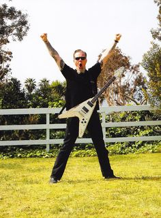 James Hetfield out in a field (perhaps his backyard?) with his old Gibson Flying V