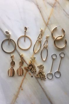 Gold and silver earrings selection by The Hexad Jewelry. Clockwise from top left: Jupiter's Orbit Earrings, Aphrodite Earrings, Usu Hoops in Gold, Eiko Earrings, Lilja Lava Earrings and the Caressa Drop Earrings. See more designs at www.thehexad.com