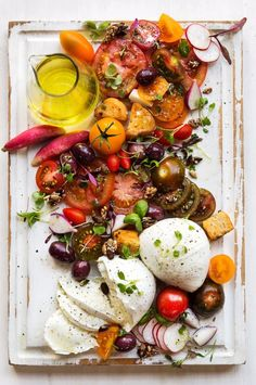 A fresh and zesty tomato salad! Pair ripe mixed tomatoes with mozzerella, olives, radishes, croutons, salt, herbs and a vinegar dressing! The perfect easy to make summer lunch! | Photography by Andrea Van Der Spuy