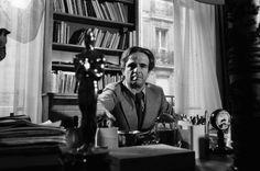 François Truffaut et son Oscar (pour La nuit américaine) devant sa bibliothèque.