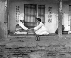 Using a grinding stone. That's beautiful calligraphy beside the door. Signage? Early Japanese Colonial Period postcard art/photography.