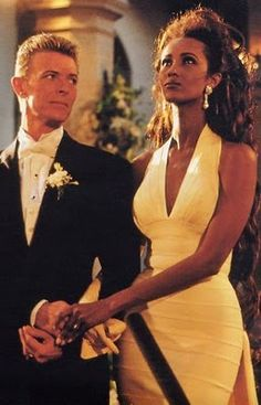 Iman (in Herve Leger) & David Bowie at their 1992 wedding in Florence, Italy.  His gaze says it all.