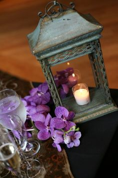 simple elegance - wrap orchid around a lantern centerpiece (but have it swirl top to bottom)
