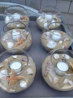 DIY beach themed Wedding Table Center Pieces - seashells, sand, tea light candles, glass bowls.