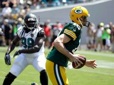 Green Bay Packers quarterback Aaron Rodgers (12) runs for a 6-yard touchdown past Jacksonville Jaguars defensive tackle Sen'Derrick Marks (99) during the first half of an NFL football game in Jacksonville, Fla., Sunday, Sept. 11, 2016.