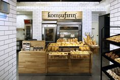 """In its fewer than five years of existence, Komsufirin has grown to some 60 stores in Turkey and it sells predominantly pre-baked products.    The store name translates as """"the oven in the neighborhood"""" and Autobahn principals Seyhan Özdemir and Sefer Cağlar used natural oak and white tiles to create a modern and visually spacey environment as a backdrop for the ancient process of baking."""