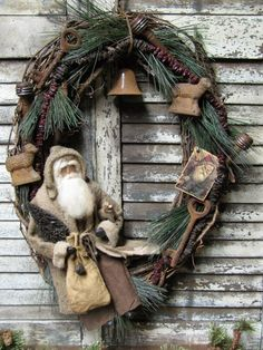 """1897 House Primitives. Olde St. Nick is dressed in vintage wool and sits on a wreath measuring 21 inches tall and 16 inches across. Details include ... A grapevine wreath with a (hand strung) dried raisin and cranberry garland, greenery, a large """"rusty"""" bell, two antique spindles, a Santa hang tag, two large skeleton keys, a painted bottle brush tree, and a German style putz sheep."""