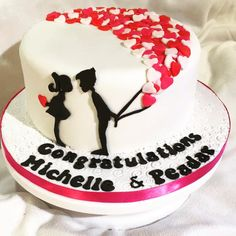 Engagement cake with couple silhouette and heart balloons.
