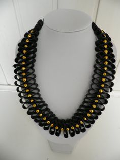 Handgemaakte rubber ketting.Het rubber is zwart.Tussen het rubber zitten gouden kralen.De ketting is 53 cm lang. De ketting is 3 cm breed.