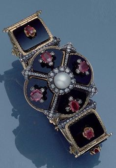 Louis Cartier - An antique gold, onyx, ruby and diamond hinged bracelet, circa 1870. The quatrefoil onyx plaque intersected by a pearl and four lines of rose-cut diamonds, each lobe applied with an oval-cut ruby and rose-cut diamond motif, on a bracelet of rectangular onyx and oval-cut ruby links with engraved gold borders and fleur-de-lys connections, maker's mark for Louis Cartier, French assay mark. #LouisCartier #Cartier #antique #bracelet
