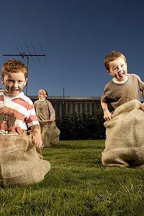 Outdoor-Bewegungsspiel – möge der Beste gewinnen! Diese Outdoor-Wettkämpfe sind ideal für Kinder: Ultimate-Frisbee, Sackhüpfen, Staffellauf, Bobby-Car-Rennen, usw...