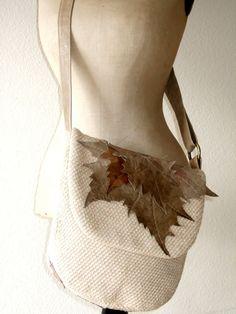 Sandfarbene Umhängetasche mit einer großen Taschenklappe, in die alles Wichtige hinein passt. Beigebraune Blätter aus unterschiedlichen Lederarten verzieren die Klappe.    Dazu passend eine kleine Clutch, auch diese ist mit Blättern dekoriert. Sie kann separat getragen werden, oder mit dem Karabiner an die große Tasche gehängt werden.        Materialien: Baumwoll-, Viskosegemisch, Innenfutter: Baumwolle      Verschluss: Magnetverschluss