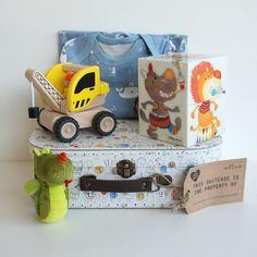 Vrolijk koffertje met babyspeelgoed en een lief pyjamaatje. In het koffertje zitten een schattig blauw pyjamaatje met walvissen van Fresk, een houten kraanwagen en leuke kartonnen blokken met circusfiguren van het merk Lilliputiens.