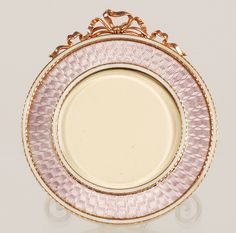 A Faberge gold and guilloche enamel frame, Moscow, circa 1896-1908. Of circular form, the surface decorated in translucent mauve enamel over a radiating engine-turned ground, between thin bands of opaque white enamel, the frame surmounted by an undulating rose gold bowknot.