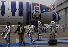Cosplayers, dressed up as stormtroopers, walk in front of the All Nippon Airways plane
