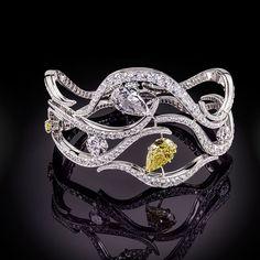 Star Diamond Diamond Bracelet. Set In 18K White Gold. Set with fancy intense yellow diamonds & white diamonds with gemstones  pivoting around the design making it sparkle & shimmer beautifully.