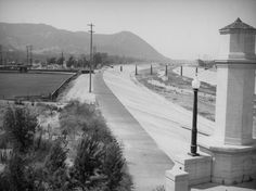 "1938-New L. A. River channel from the Glendale-Hyperion Bridge The path of the Los Angeles River is contained in a new concrete channel, although there is still a natural river bottom, in this view looking north taken from the 1927 Glendale/Hyperion Bridge (originally known as the ""Victory Memorial Bridge"" in honor of World War I veterans). Posts across the river will become a pedestrian bridge at Sunnynook Drive, which is still there today. The south side of Griffith Park can be seen in the…"