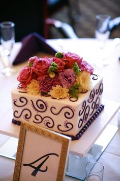 Square cake with brightly colored fresh flowers.