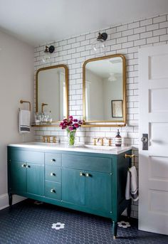 Gorgeous traditional bathroom with modern finishes -- love the combination of brass sink fixtures, glass knobs on the painted teal cabinets, golden brass oversized bathroom mirrors, white subway tiles with gray grout and the classic navy blue penny tiles on the floor.