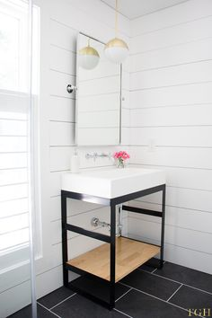 White modern bathroom makeover featuring a steel vanity, wall mounted faucet, trough sink and shiplap