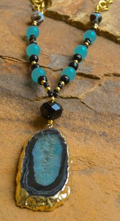 """Aqua agate, black onyx, gold beads and chain with gold trimmed aqua and black pendant. Necklace is 32"""" in length with a 3"""" extender. Customization available upon request."""