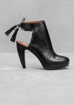 Feminine and chic, these high heel leather boots feature a high, sculpted heel and a fringed ankle strap.