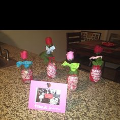 Such a cheap cute table top idea! Mason jars filled w rose pedals and napkin quotes! Then fake roses w ribbon tied around them!