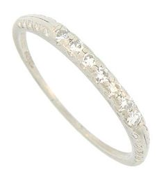 This is my wedding band!! And I ♥ it :)  Seven deep set fiery diamonds adorn the face of this antique platinum wedding band. Organic engraving stretches down the shoulders and sides of this Edwardian wedding ring. The ring measures 2.08 mm in width. Circa: 1910