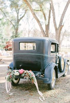 Brides.com: . This vintage getaway car is dressed up with a mix of pink and white flowers, lush greenery, and trailing ribbon for the perfect splash of color against the black paint.