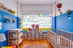 Quarto de gêmeos com parte da parede pintada de azul, berços da Ikea e cortina feita com tecido da Marimekko.
