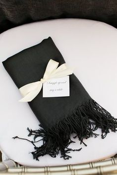 For an outdoor wedding in a colder month, place pashmina scarveson the seats of female guests (Photo by Nancy Aidée Photography)