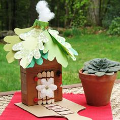 """""""Cardboard box,Craft knife,Scissors, 4 craft sticks, 2 pipe cleaners, Glue dots, 2 flat buttons and 1 shank-style button,Pushpin,silk flower,Thin string,Small bell,,3 5oz paper cups,Stapler,paper green,Cotton ball, Corrugated cardboard 1.cut 4x2½-in door 2.craft sticks side-by-side bend pipe cleaners the tops & bottoms 3. pushpin to poke hinges in cardboard alongside door openingfor each hinge, thread one of the adjacent pipe cleaner ends through the hole and then twist the two ends together."""""""