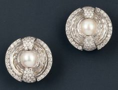 BOIVIN  Pair of clip-on earrings in platinum and rock crystal round. Rock crystal carved northlight door to a large pearl center and is bord...
