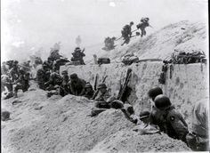 Soldiers of the 8th Infantry Regiment, 4th Infantry Division, move over a seawall on Utah Beach during the Allied Invasion of Europe