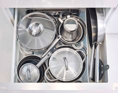 Open IKEA drawer with pots and pans inside, kept in place with a drawer divider.