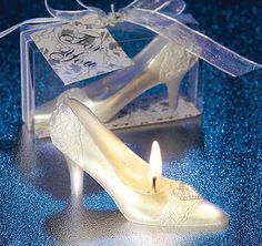 "These Fairytale Shoe Candles are perfect for a fairytale wedding, bridal shower, Quinceanera or a Sweet 16 celebration.  Each candle is made of off-white wax and has an exquisite filigree floral design, including a centerpiece heart-shaped buckle.  Candle comes packaged upright in a clear plastic box and has an elegant silver and white floral base.  A white organza ribbon and a matching ""For You"" tag completes the favor."