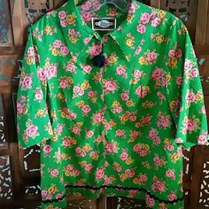 """Vintage Green and Pink Floral Top 1960s or 1970s green top with pink and yellow floral design. Made by Mary Mackenzie Boutique. Zips almost all the way down the front. Black tassel zipper pull. Black rickrack trim. Boxy style. Slightly belled sleeves. Measures about 19"""" flat across chest armpit to armpit. Probably cotton or a cotton blend. Good vintage condition. Vintage Tops"""