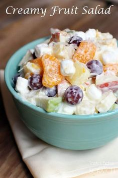 A blue bowl sitting on a napkin and filled with grapes, mandarin oranges, apples, marshmallows, and a Greek yogurt dressing.