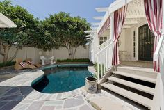 Love the striped curtains and matching sunshade.  The little pool is perfect for a tiny bungalow.