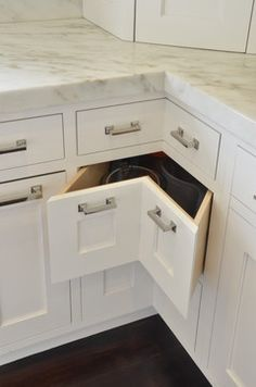 White cabinets have Hickory Hardware's Studio Pulls on corner drawers by Studio Dearborn.