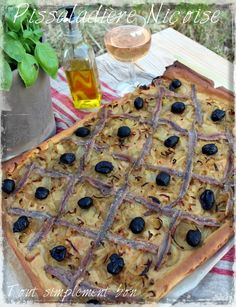 Pissaladière niçoise ~ a regional specialty. A bread-like crust is covered with caramelized onions, baked, then decorated with anchovy filets and Niçois olives. Traditionally served at room temperature with an aperitif.