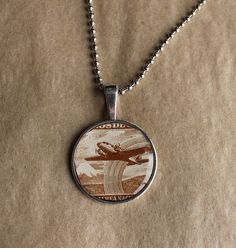Aviation themed vintage postage stamp necklace. Cute handmade jewelry by a New Orleans artist