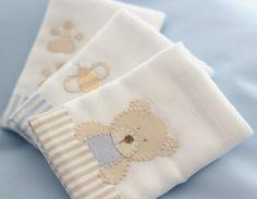 As Fraldinhas de boca são bordadas à mão com desenhos do Ursinho, suas pegadas e uma abelhinha com detalhes em azul. Feitas em algodão, têm barra de tecido listrado, tema da coleção. São 03 unidades de 32 x 32 cm cada.