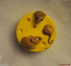 Bakelite button featuring three vegetable ivory mice in a wheel of cheese. On ebay.