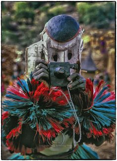 A Dogon man imitates a white tourist in a masked dance. The Dogon dancer (from Mali, West Africa) carved his 'white man' mask and camera from solid wood, painting both and stringing his wooden camera with rope. Photo by Rosemary Sheel, 2000