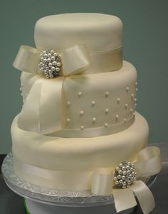 Ivory wedding cake with ivory ribbon, bow, and broach.  I love the simple elegance!