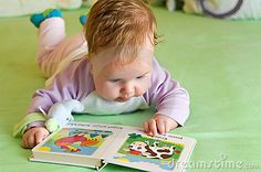 Cute baby girl reading a book on bed.